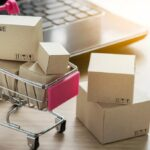Paper shopping small box express in a shopping cart and laptop notebook on wood table background. Online shopping concept.